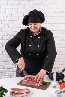 Kobieta kucharz rozbioru mięsa