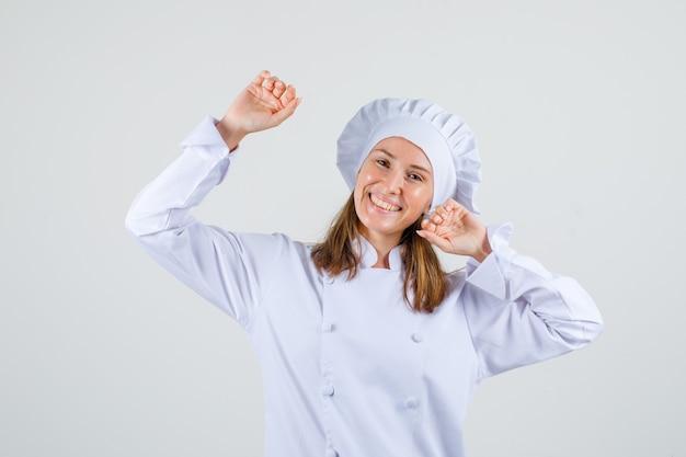 Kobieta kucharz, rozciągając ramiona w białym mundurze i patrząc wesoło