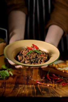 Kobieta kucharz serwująca tradycyjne tajskie jedzenie, zamieszać smażoną mieloną wieprzowinę z bazylią (pad ka prao) na talerzu vintage