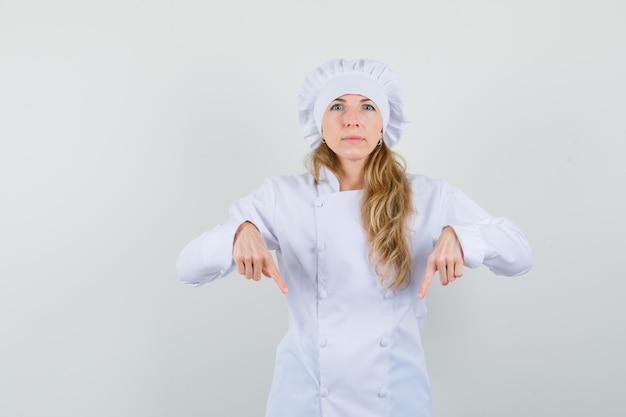 Kobieta kucharz skierowaną w dół w białym mundurze i patrząc pewnie.