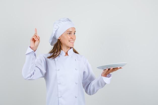 Kobieta kucharz skierowaną w górę, trzymając talerz w białym mundurze i patrząc zadowolony