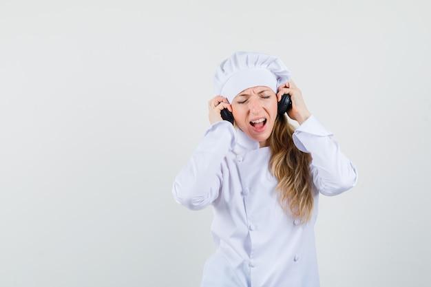 Kobieta kucharz słucha muzyki w słuchawkach w białym mundurze i wygląda na zachwyconą