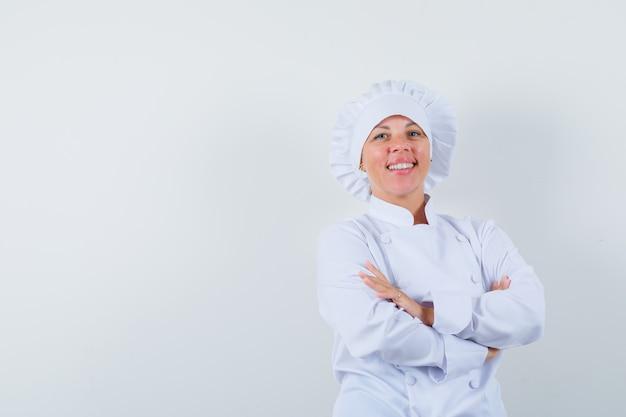 Kobieta kucharz stoi ze skrzyżowanymi rękami w białym mundurze i wygląda pewnie