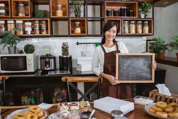 Kobieta kucharz trzyma czarną tablicę stojąc w kuchni