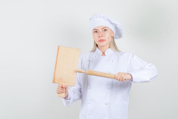 Kobieta kucharz trzyma deskę do krojenia i wałkiem do ciasta w białym mundurze i wygląda poważnie