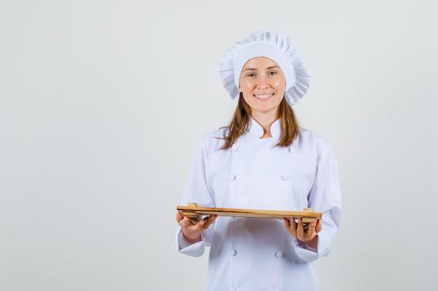 Kobieta kucharz trzyma drewnianą tacę w białym mundurze i wygląda wesoło. przedni widok.