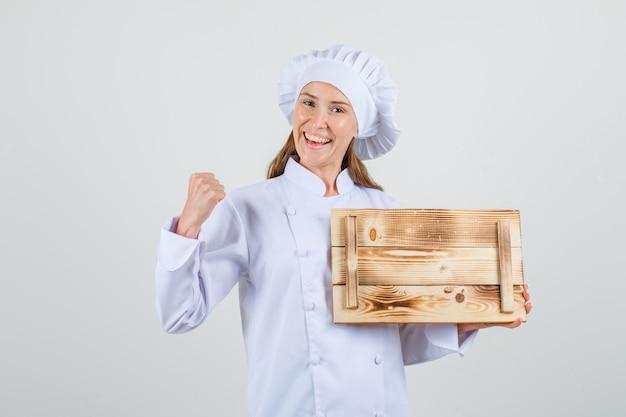 Kobieta kucharz trzyma drewnianą tacę z zaciśniętą pięścią w białym mundurze i wygląda wesoło