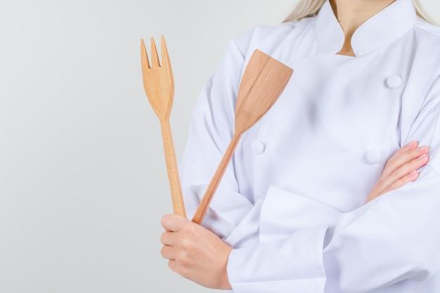 Kobieta kucharz trzyma drewniany widelec i szpatułkę w białym mundurze