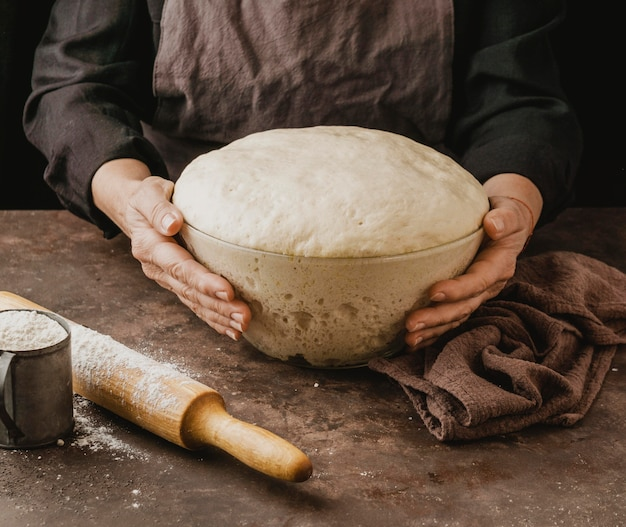 Kobieta kucharz trzyma miskę z ciasta do pizzy