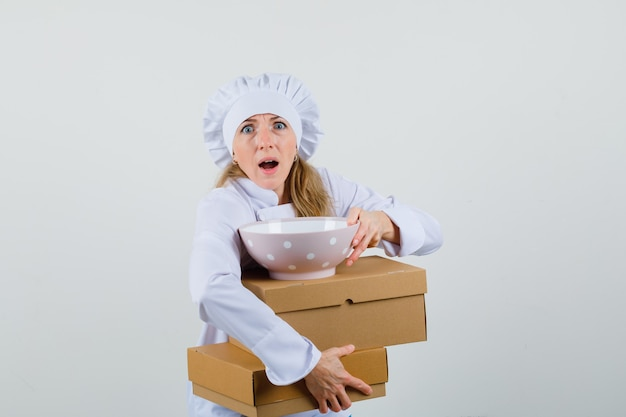Kobieta kucharz trzyma miskę z kartonów w białym mundurze