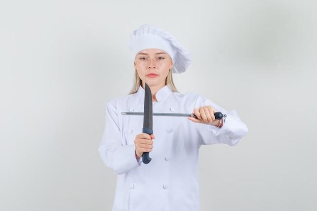 Kobieta kucharz trzyma nóż i ostrzałkę w białym mundurze i wygląda poważnie