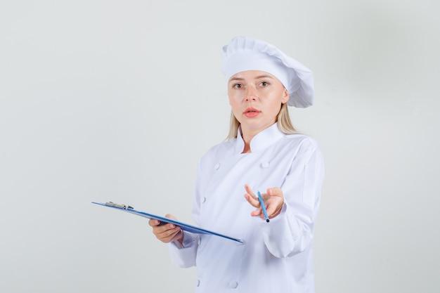 Kobieta kucharz trzyma schowek z ołówkiem w białym mundurze i wygląda zdezorientowany
