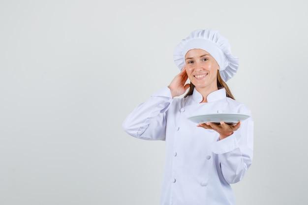 Kobieta kucharz trzyma talerz w białym mundurze i wygląda na szczęśliwego
