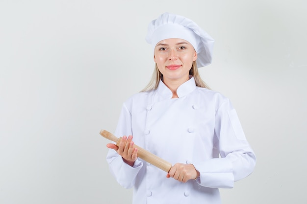 Kobieta kucharz trzyma wałek do ciasta w białym mundurze i wygląda wesoło.