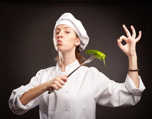 Kobieta kucharz trzyma zielonego pieprzu z widelcem