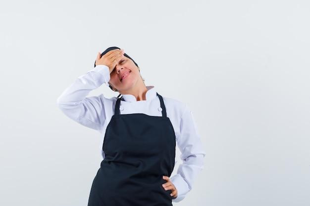 Kobieta kucharz trzymając rękę na czole w mundurze, fartuchu i wyglądający elegancko, widok z przodu.