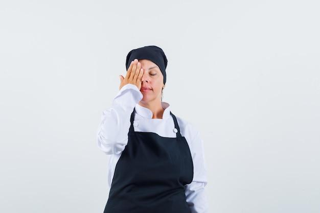 Kobieta kucharz trzymając rękę na oku w mundurze, fartuch i patrząc spokojnie, widok z przodu.