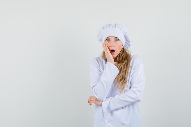 Kobieta kucharz, trzymając rękę na policzku w białym mundurze i patrząc zszokowany