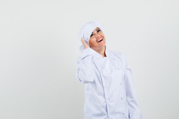 Kobieta kucharz trzymając rękę w pobliżu ucha w białym mundurze i patrząc wesoło