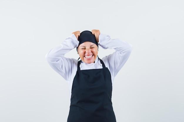 Kobieta kucharz trzymając się za ręce na głowie w mundurze, fartuchu i patrząc szczęśliwy, widok z przodu.
