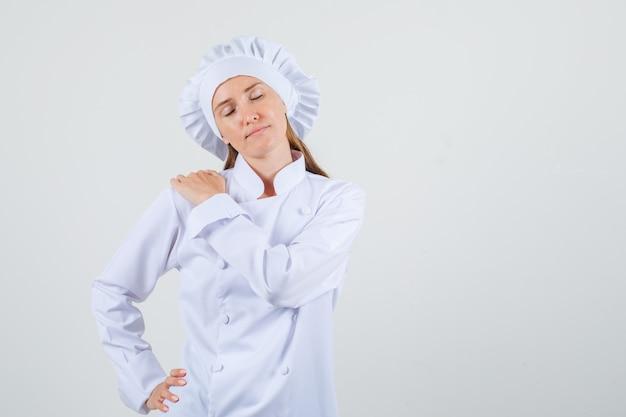 Kobieta kucharz, trzymając się za ręce na ramieniu i talii w białym mundurze i wyglądający na zmęczonego. przedni widok.