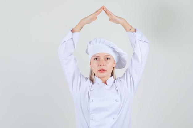 Kobieta kucharz trzymając się za ręce nad głową jako dach domu w białym mundurze