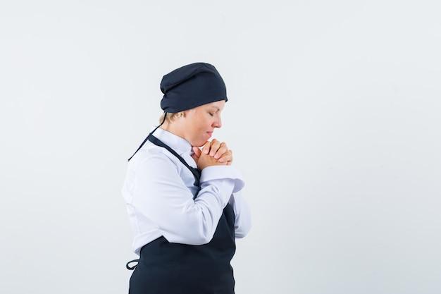 Kobieta kucharz trzymając się za ręce splecione w mundur, fartuch i marzycielski wygląd. przedni widok.