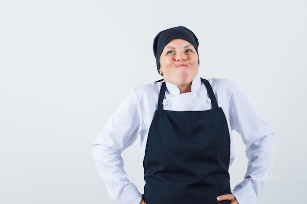 Kobieta kucharz, trzymając się za ręce w pasie w mundurze, fartuchu i patrząc zdezorientowany. przedni widok.