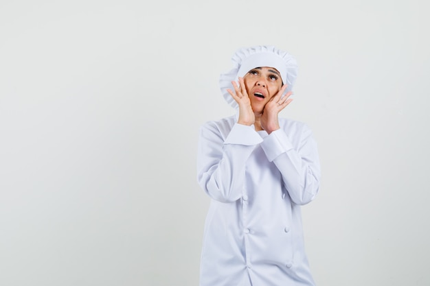 Kobieta kucharz trzymając się za ręce w pobliżu ust w białym mundurze i wyglądający zmartwiony