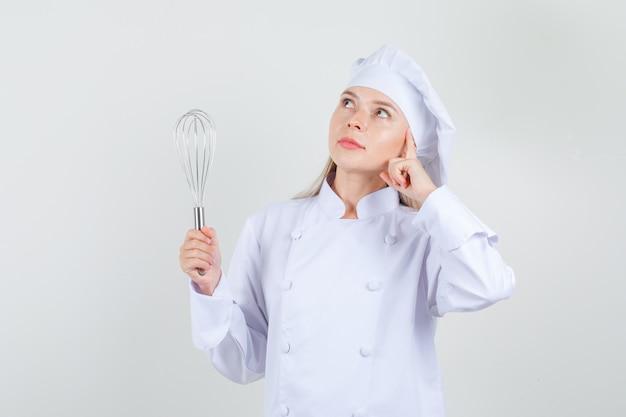 Kobieta kucharz trzymając trzepaczkę i patrząc marzycielsko w białym mundurze