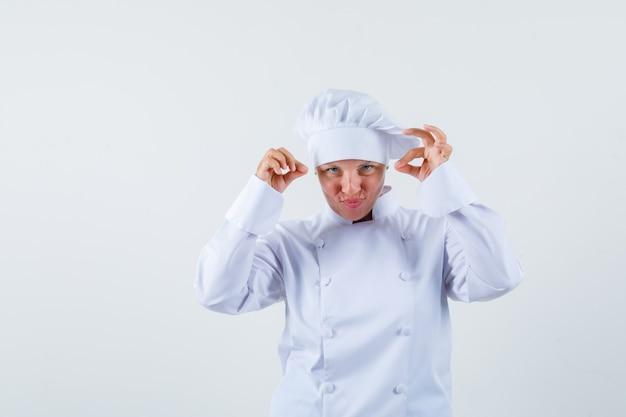 Kobieta kucharz udająca posypywanie solą w białym mundurze i wyglądająca na skupioną