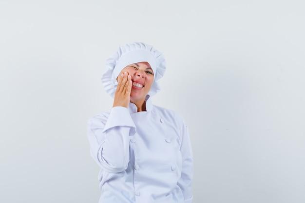 Kobieta kucharz w białym mundurze, ból zęba i niewygodny wygląd