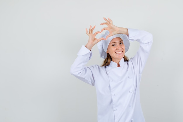 Kobieta kucharz w białym mundurze co kształt serca i wygląda szczęśliwy