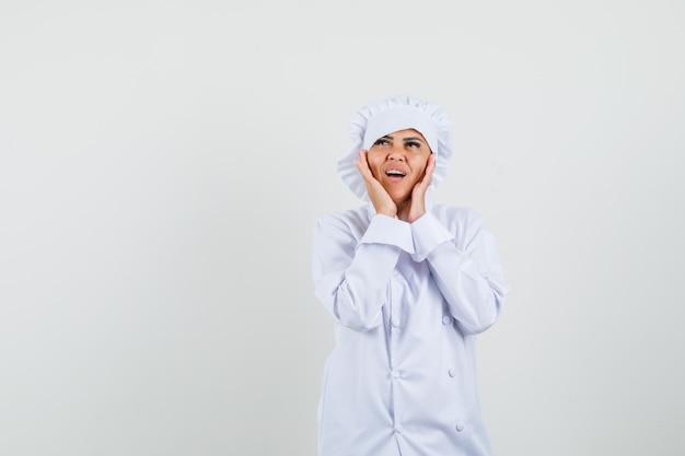 Kobieta kucharz w białym mundurze, dotykając policzków rękami i patrząc zamyślony
