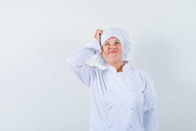 Kobieta kucharz w białym mundurze drapiąc się po głowie i patrząc zapominalski