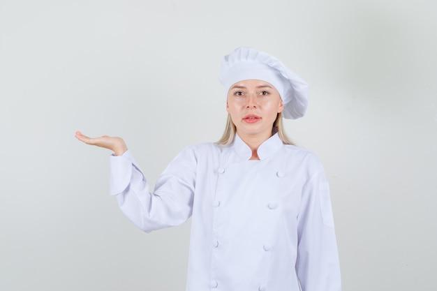 Kobieta kucharz w białym mundurze gestykuluje jak coś trzyma