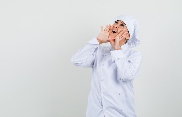 Kobieta kucharz w białym mundurze krzyczy lub coś ogłasza