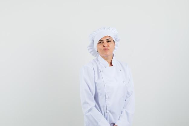 Kobieta kucharz w białym mundurze patrząc na kamery i patrząc pewnie