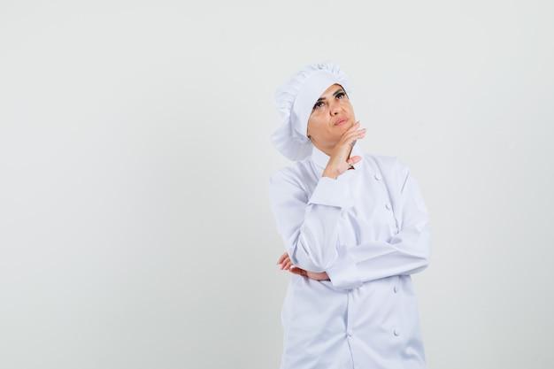 Kobieta kucharz w białym mundurze, patrząc w górę i zamyślony