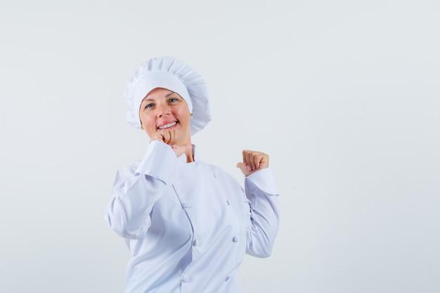 Kobieta kucharz w białym mundurze pokazując gest zwycięzcy i patrząc zadowolony