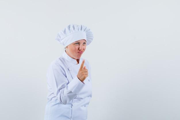 Kobieta kucharz w białym mundurze pokazuje gest ostrzegawczy i wygląda uważnie