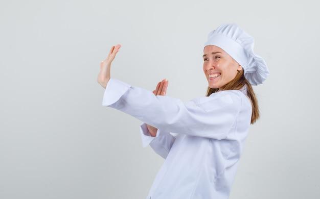 Kobieta kucharz w białym mundurze pokazuje gest stopu śmiejąc się i patrząc przestraszony.