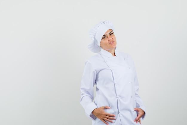 Kobieta kucharz w białym mundurze pozowanie, stojąc i patrząc pewnie