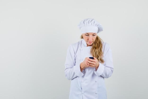 Kobieta kucharz w białym mundurze przy użyciu telefonu komórkowego i patrząc zajęty