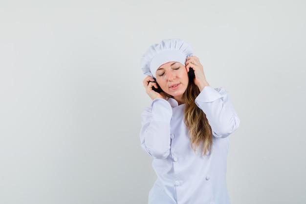 Kobieta kucharz w białym mundurze, słuchając muzyki w słuchawkach