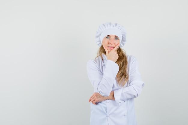 Kobieta kucharz w białym mundurze, stojąc w myśleniu poza i wyglądający rozsądnie