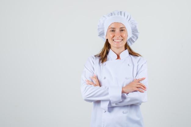 Kobieta kucharz w białym mundurze, stojąc ze skrzyżowanymi rękami i wyglądając wesoło