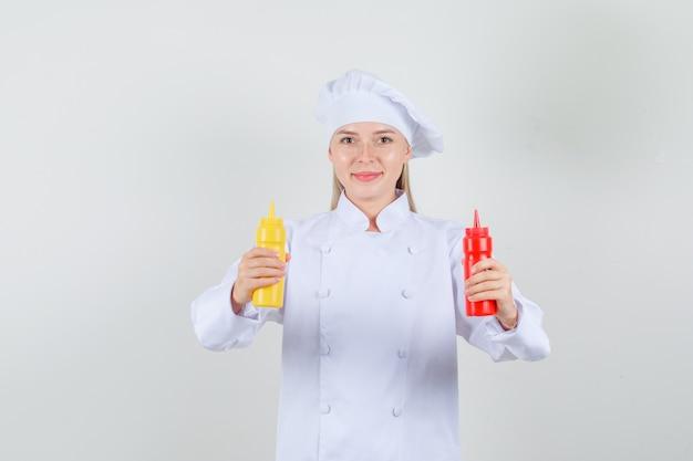 Kobieta kucharz w białym mundurze, trzymając butelki keczupu i musztardy i patrząc wesoło