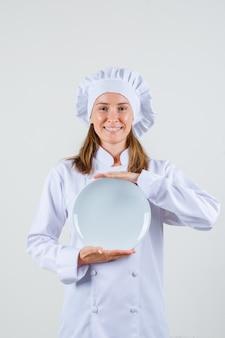 Kobieta kucharz w białym mundurze, trzymając pusty talerz i patrząc zadowolony.