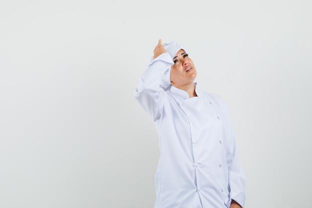 Kobieta kucharz w białym mundurze, trzymając rękę na głowie i patrząc smutno